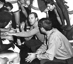 Coach Fletcher Arritt huddles with his team during a game in the 1970s