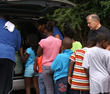 Line of children at Seton Youth Shelters' Street Outreach Van to receive snacks, counseling, clothing and other items.