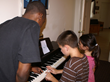 Residents learning to play the piano in Seton Youth Shelters' home-like shelters.