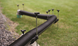 The durable Flow Down adjustable RV drain support system is used to keep an RV drain hose up off of the ground and easily adjusts to nearly any slope, allowing sewage to properly drain and helping to prevent anything from getting trapped in the hose.