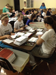 Students from St. Gabriel Middle School volunteer at Unbound, stuffing letters to sponsors to get mailed out.