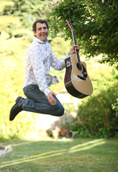 Singer Songwriter Michael Ryther jumps with guitar