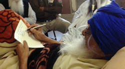 File photo of Surat Singh Khalsa writing a note to his supporters