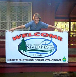 """Wendy Austin rolls out the """"welcome"""" sign at FOLAR RiverFest.."""