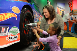 Families and their friends race the clock to change tires and refuel a car at The Children's Museum of Indianapolis.