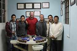 Crimson Cup coffee buying team Greg Ubert and Dave Eldgridge (center) cup coffee with De Leon family in Guatemala