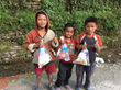 Three Nepalese boys give the volunteers a smiling thumbs up for their help.