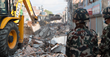 A JCB backhoe loader pictured on Tuesday, May 12 in Kathmandu, Nepal, clearing debris from the site of a building that collapsed in the country's second earthquake.
