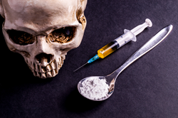 heroin and needle with skull