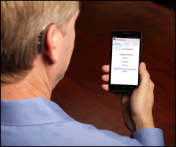 A man is wearing a Companion hearing aid and using his smartphone to program his device