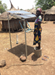 Aishetu, who runs the solar business in Tacpuli, cleans the solar panels. These panels provide energy to the charging station created by the Saha Global and Next Step Living partnership.
