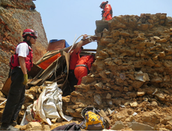 Los Topos and CINAT members enter the significantly damaged temple in Kathmandu on May 24 on an operation to salvage precious artifacts trapped beneath the structure's collapsing roof.