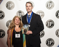 S. Chris Shirley, author of Playing by the Book, and his publisher, Lori Perkins, pose for a press photo after winning a National Medal in Religious Fiction at the 19th Annual IPPY Awards in New York City