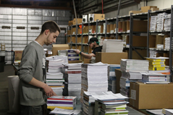 Employees at the ProLiteracy warehouse prepare New Readers Press books for shipment.