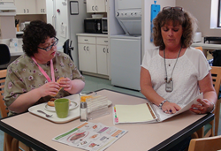 Cheryl Ollis goes over a list of meals for the week with student Jessica Bejarano.
