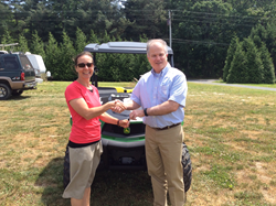Martin Desmond, area lending manager with MidAtlantic Farm Credit, hands Marcia Spence the keys to her new John Deere Gator.