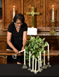 Ms. Geraldine Hayes, whose high school friend, Rev. Daniel L. Simmons, was gunned down in Charleston Wednesday, lights a candle for each ¬the nine victims June 18, 2015, at an all-faith prayer vigil at the First AME Church in Los Angeles.