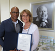 Sacramento Vice Mayor Allen Warren presents Scientologist Patty Cota with a certificate of appreciation for her volunteer work.