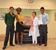 Emah Madegwa hands over a 10-Gallon TakeAway Environmental Return System to JiYang Chung, pharmacy manager at Benzer Pharmacy located in Tampa