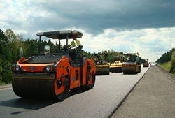 Multiple intelligent compaction rollers compact asphalt during pavement construction.