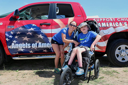 Event organizer, Lisa Keys, stands with her son Ethan next to Angels of America's Fallen event vehicle.