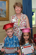 Harbor House Administrator Susan Jessup presents Alexander Thorton, age 5, and Adriana Teixeira, age 5, with their 2015 graduation diplomas. Both will attend kindergarten next year.