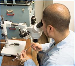 An Advanced Endoscopy Devices technician inspecting an optical forcep.