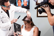 Dr. Alan Bauman examines the affected area of the scalp prior to CNC hair system application