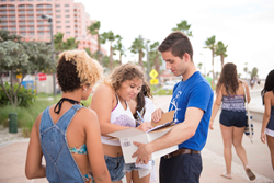 Volunteer encourages beach-goers to sign a petition to mandate education on the Universal Declaration of Human Rights.