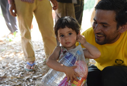 A little girl carries a food pack almost bigger than she is. Lead Volunteer Minister Binod Sharma met her while he and his team distributed food and water to families left homeless by the April 2015 Nepal earthquake.