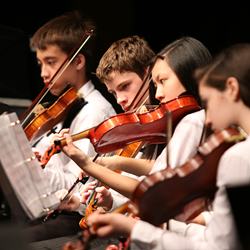 Young violin students performing at a school concert.