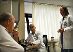 Dr. Anthony Jabre (center), Neurosurgery Section Chief, Bay Pines VA Healthcare System and Martha Beach (right), Advanced Registered Nurse Practitioner, meet with Marine Corps Veteran Bruce Guerin during an appointment at the C.W. Bill Young VA Medical Ce