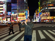Tom (Jonathan Sherr) taking a photo in Tokyo