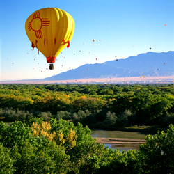 The New Mexico Zia sun symbol (State Flag) balloon over the Rio Grande Valley. Photo by MarbleStreetStudio.com