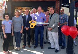 Greg Ubert (center) and members of the Upper Arlington Chamber of Commerce cut the ribbon at the grand opening of the Crimson Cup Coffee House in Upper Arlington