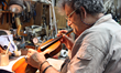 Amnon Weinstein restoring a violin, photo courtesy of Debra Yasinow and the Jewish Federation of Cleveland
