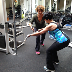 Personal trainer Althea Hondrogen working with a client performing a standing row.