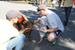 "Parents David and Natalie Oliver and their baby make friends with ""Piper"" LoGrasso, a lab/pitbull mix (adopted through Adopt-A-Dog) at the 28th Annual Puttin' on the Dog"