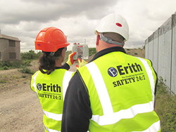 Construction site workers using a hand-held Shawcity monitor to measure air quality and dust levels