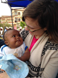 Edgar holding a baby while visiting Unbound's program in Madagascar.
