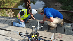 Dustin Berry and Travis Fields on bridge during inspection with drone