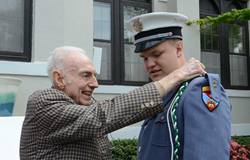 "Eric Nelson, Greenbrier Military School Class of 1947, helps attach the Greenbrier Cadet cord to the uniform of his grandson, Cadet Robert ""Bo"" Barnes."