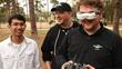 Peter Sripol and Josh Bixler watch as Alex Zvada pilots a racing drone.