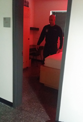 Firefighter exits illuminated dorm room at the station during a Phoenix G2 automated dispatch alert