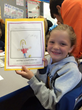 Photo of Barnhart School First Grader and her Writer's Workshop Project at the Publishing Party