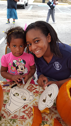Rosarian-Academy-student-Laura-Narcisse-8th-grade-decorates-Halloween-mask-with-resident-of-The-Lord's-Place