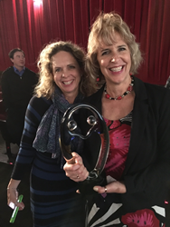 Kris Warner, executive assistant, and Faye Oney, marketing coordinator accept the award for Pearl