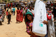 A woman in Nepal carries a Shelter Kit provided by ShelterBox