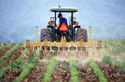 New report warns of climate change threats to food security - farmer tilling soil