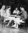 Famous American ex-pat and author Ernest Hemingway (left) exchanges ideas with friends at a European cafe in 1925.